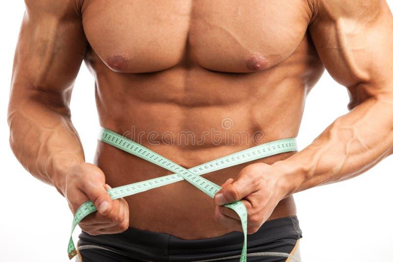 Punto di vista potato di giovane uomo muscolare con nastro adesivo di misurazione immagini stock libere da diritti