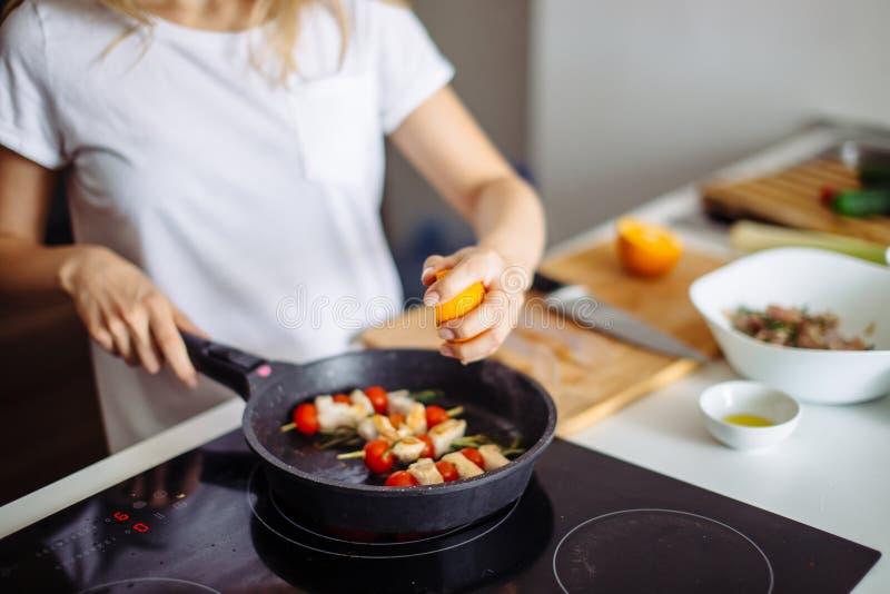 Punto di vista potato di giovane casalinga felice che frigge carne di pollo per la cena fotografie stock libere da diritti