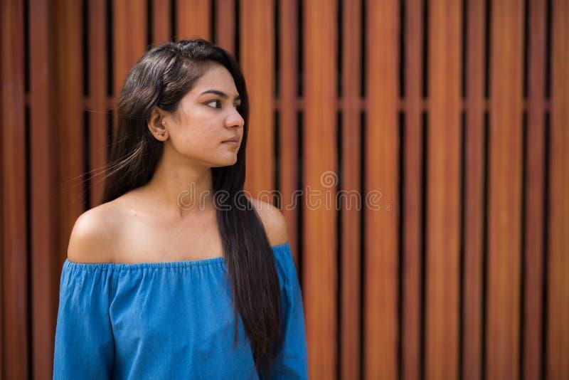 Punto di vista di profilo di giovane donna indiana che pensa mentre esaminando DIS fotografia stock libera da diritti