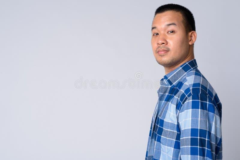 Punto di vista di profilo di giovane uomo asiatico dei pantaloni a vita bassa che esamina macchina fotografica fotografie stock libere da diritti