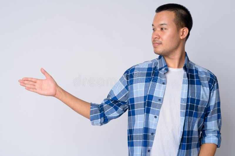 Punto di vista di profilo di giovane uomo asiatico dei pantaloni a vita bassa che mostra qualcosa fotografia stock