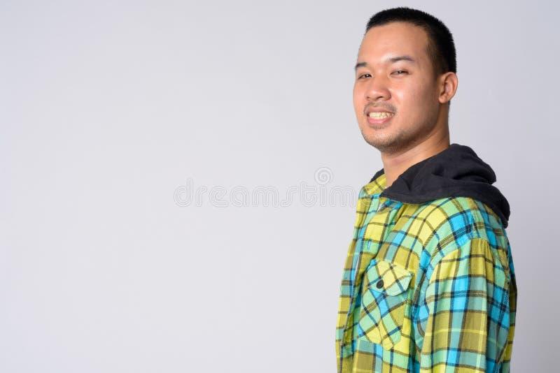 Punto di vista di profilo di giovane uomo asiatico felice dei pantaloni a vita bassa che esamina macchina fotografica fotografie stock libere da diritti