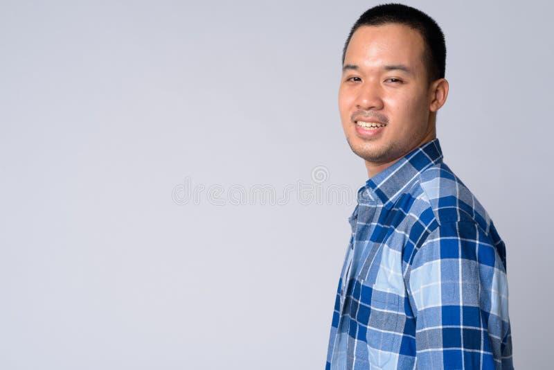 Punto di vista di profilo di giovane uomo asiatico felice dei pantaloni a vita bassa che esamina macchina fotografica immagini stock libere da diritti