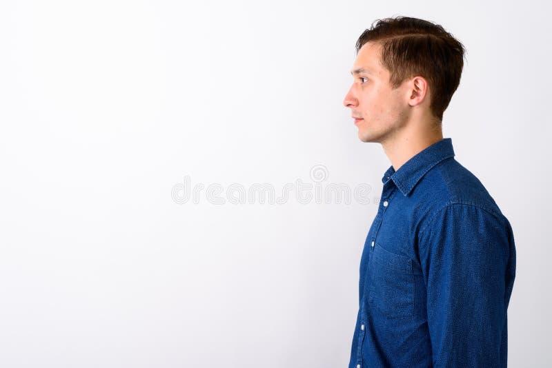 Punto di vista di profilo di giovane uomo bello contro fondo bianco fotografia stock libera da diritti