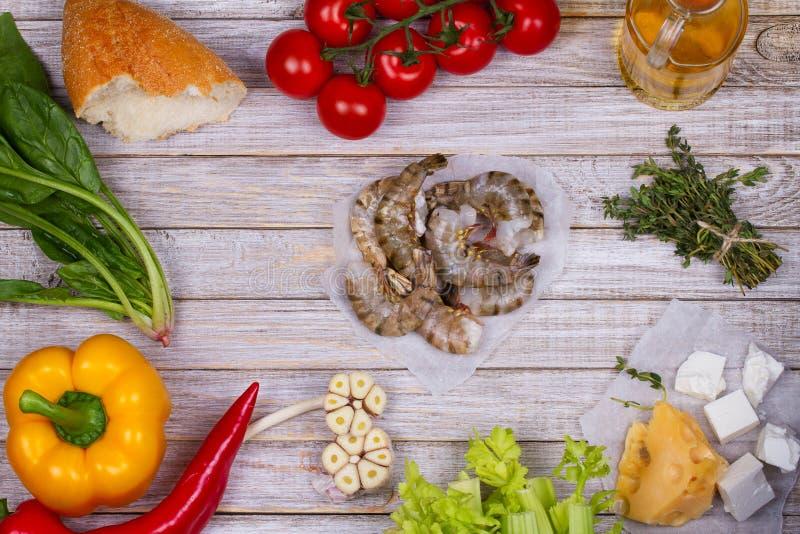Punto di vista sopraelevato dei gamberetti, spinaci, peperone dolce, ciliegia del pomodoro, pane, aglio, timo, Olive Oil, vetro d fotografie stock libere da diritti