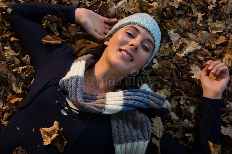 Punto di vista sopraelevato della donna che si trova sulle foglie asciutte immagine stock