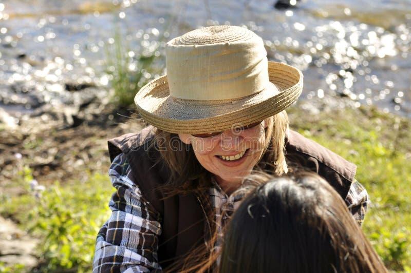 Punto di vista sopraelevato della donna di mezza età nella conversazione che sorride con l'amico immagini stock