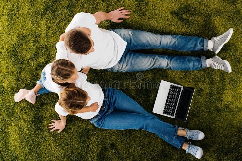 punto di vista sopraelevato della famiglia con il riposo del computer portatile fotografia stock