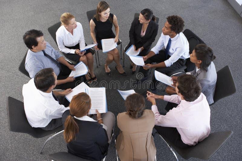 Punto di vista sopraelevato delle persone di affari messe nel cerchio al seminario della società immagini stock