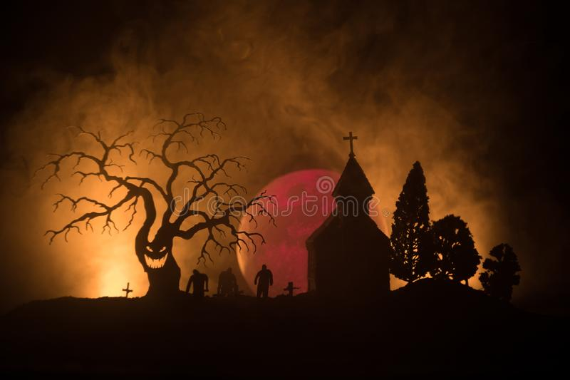 Punto di vista spaventoso degli zombie all'albero morto del cimitero, alla luna, alla chiesa ed al cielo nuvoloso spettrale con n fotografia stock