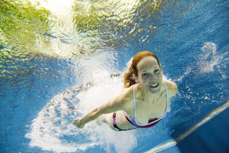 Punto di vista subacqueo di una giovane donna che salta nell'acqua fotografia stock libera da diritti