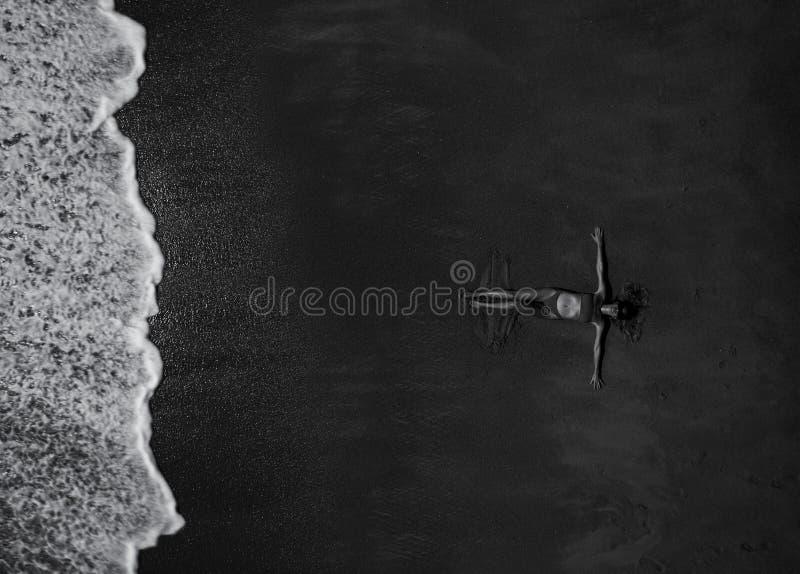 Punto di vista superiore aereo della donna con le sue mani stese mettendo sulla spiaggia sabbiosa immagini stock libere da diritti