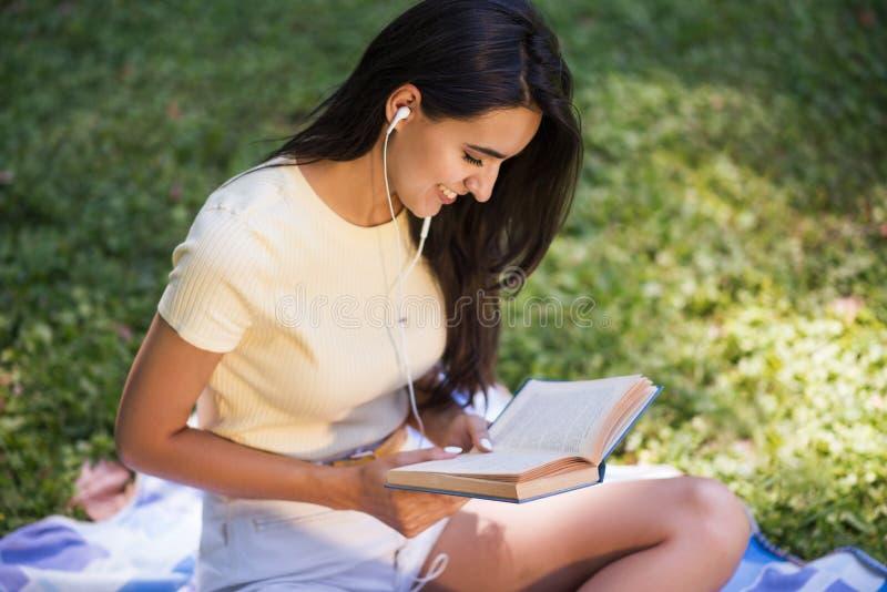 Punto di vista superiore di bella giovane donna sorridente castana caucasica con le cuffie, ascoltando la musica e leggendo un li fotografie stock