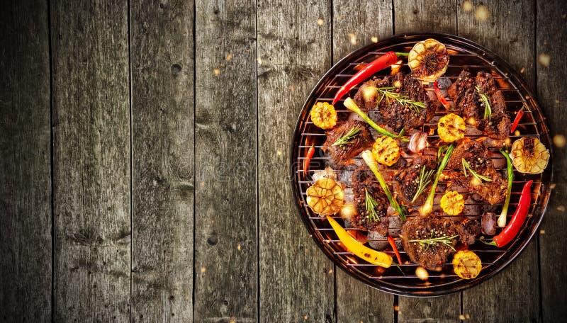 Punto di vista superiore di carne fresca e della verdura sulla griglia disposta sulla f di legno immagine stock