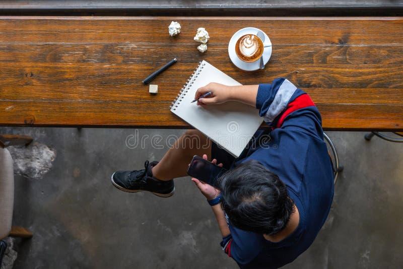 Punto di vista superiore del progettista asiatico che attinge sketchbook al caffè immagine stock