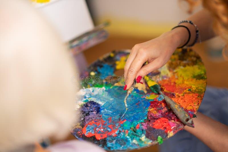 Punto di vista superiore dell'artista che prende gouache dalla tavolozza di colore immagini stock