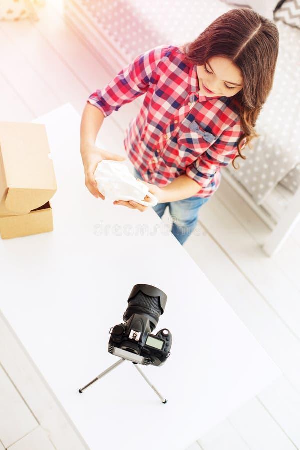 Punto di vista superiore della bambina alla moda che dice circa i suoi presente sul video di contaminazione della macchina fotogr fotografia stock
