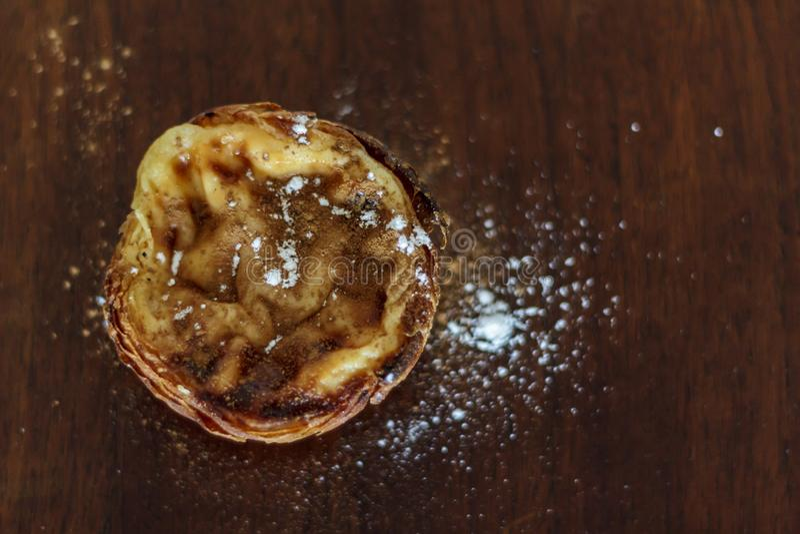 Punto di vista superiore della crostata portoghese tipica dell'uovo, Pastel de Nata, con la polvere della cannella e la polvere d fotografia stock