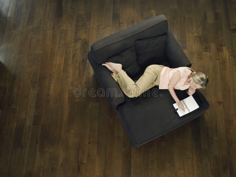 Punto di vista superiore della donna che per mezzo del computer portatile sul sofà immagini stock
