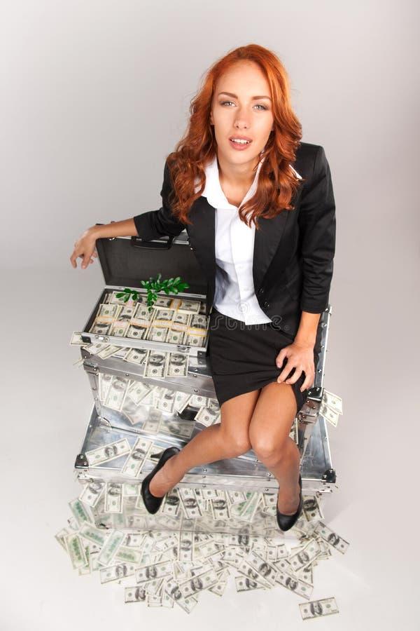 Punto di vista superiore della donna che si siede sulla valigia in pieno di soldi fotografie stock