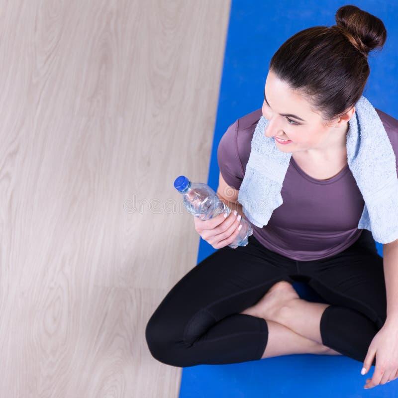 Punto di vista superiore della donna sportiva che si siede sul pavimento di legno dopo la formazione immagini stock libere da diritti