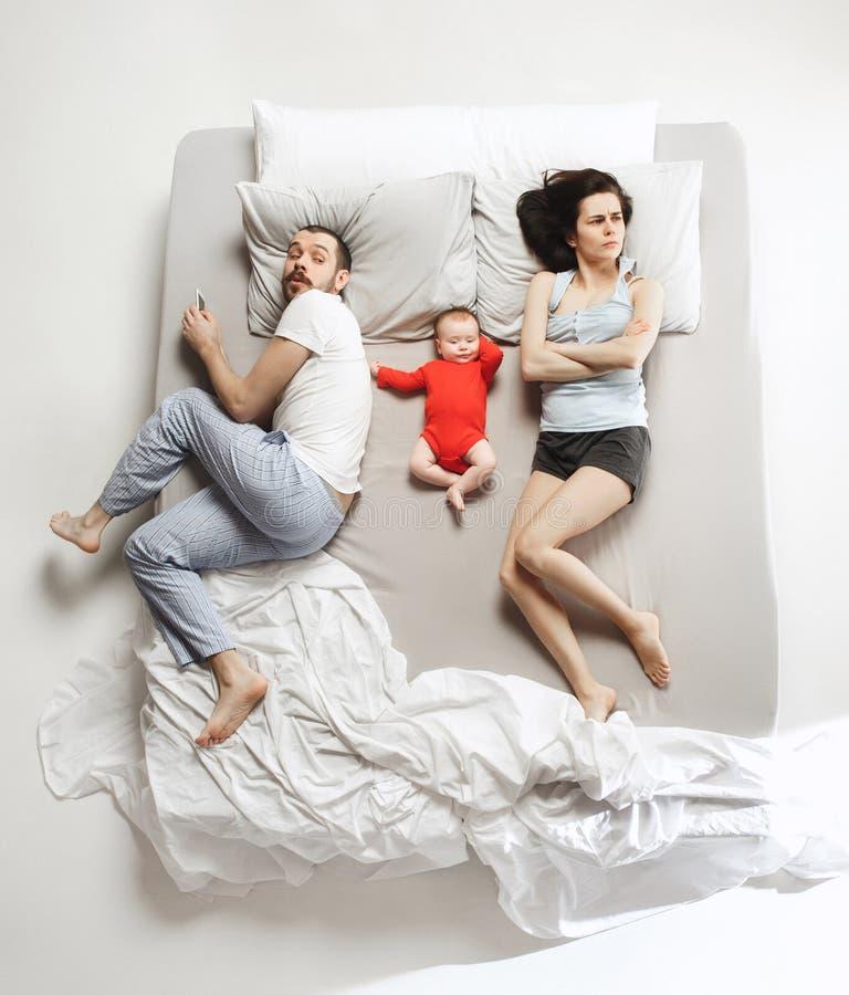 Punto di vista superiore della famiglia felice con un bambino neonato in camera da letto fotografia stock