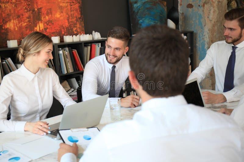 Punto di vista superiore della gente di affari che lavora insieme mentre spendendo tempo nell'ufficio fotografia stock