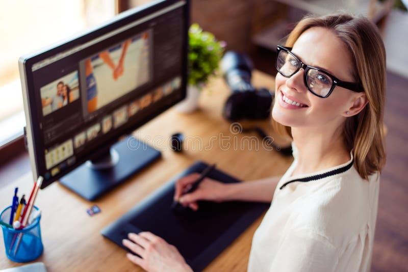 Punto di vista superiore della giovane donna bionda intelligente che lavora con il computer immagini stock