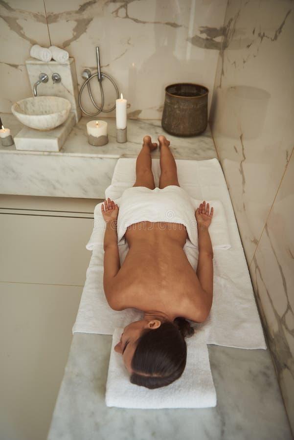 Punto di vista superiore della giovane signora che si rilassa nel bagno turco con l'asciugamano sulle sue anche immagini stock libere da diritti