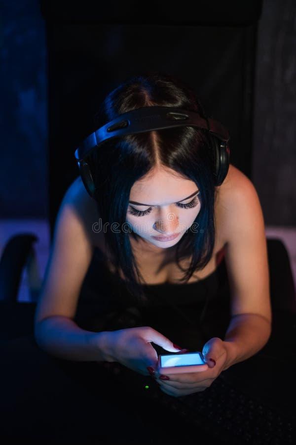 Punto di vista superiore della ragazza graziosa che si rilassa a casa, sta giocando la musica facendo uso di uno smartphone e del fotografia stock libera da diritti
