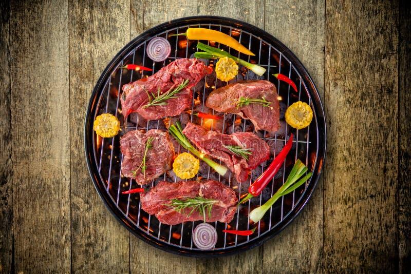 Punto di vista superiore di carne fresca e della verdura sulla griglia disposta sul pavimento di legno immagini stock libere da diritti