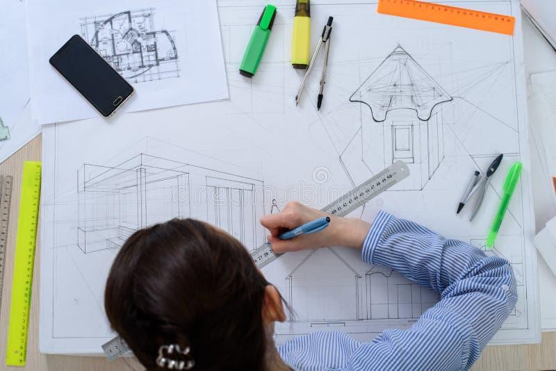 Punto di vista superiore di giovane studente che prepara lavoro architettonico ad una tavola con una carta da disegno e una cance fotografia stock libera da diritti