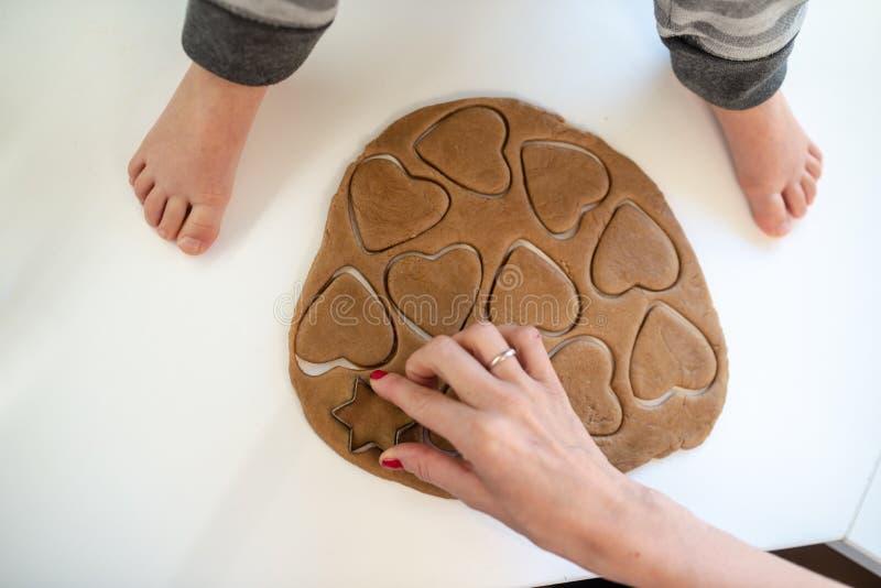 Punto di vista superiore di una madre che preme la taglierina del biscotto di forma del cuore in pasta rotolata fotografia stock