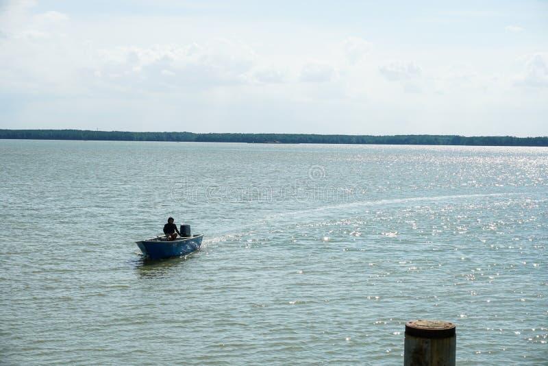 Punto di vista di un uomo che dirige una barca attraverso un fiume calmo fotografia stock libera da diritti