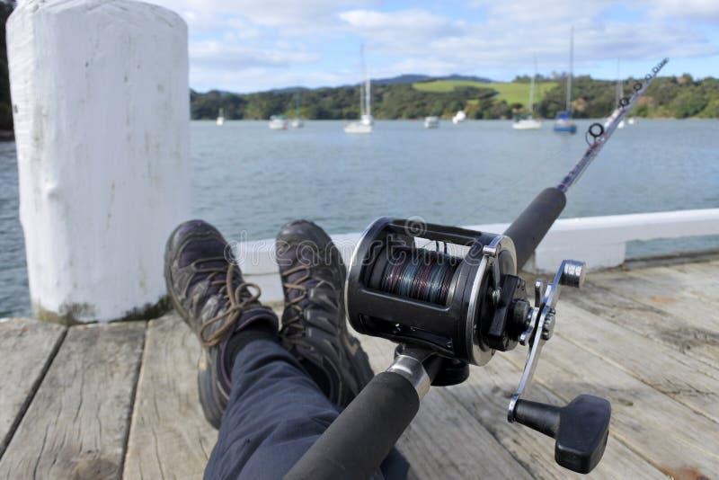 Punto di vista di una pesca dell'uomo con una canna da pesca fotografia stock