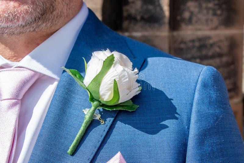 Punto di vista di uno sposo che indossa un occhiello rosa artificiale fotografia stock