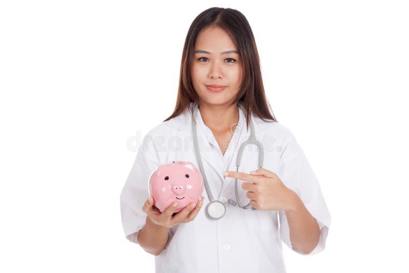 Punto femenino asiático joven del doctor a una moneda del banco del cerdo fotos de archivo