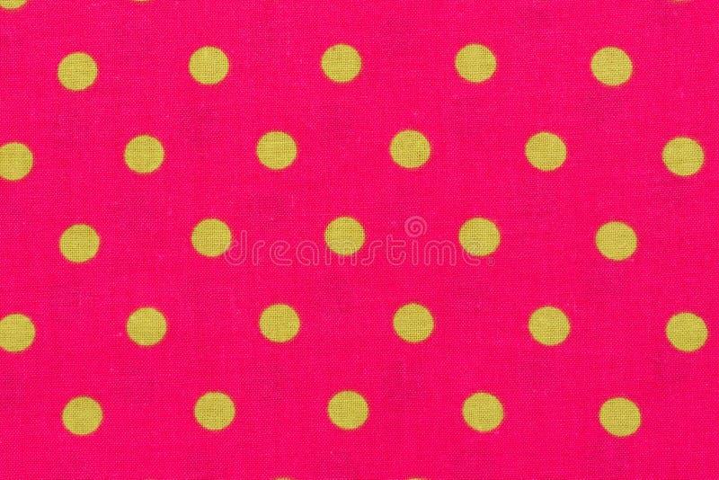 Punto giallo sopra il fondo e la struttura rosa del tessuto del pois immagine stock
