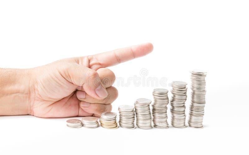 Punto masculino de la mano a la pila de la moneda del dinero imagenes de archivo