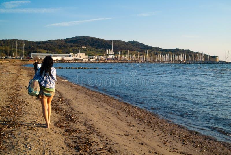 Puntone斯卡尔利诺,Maremma托斯卡纳,意大利 走在海滩的成熟妇女 库存图片