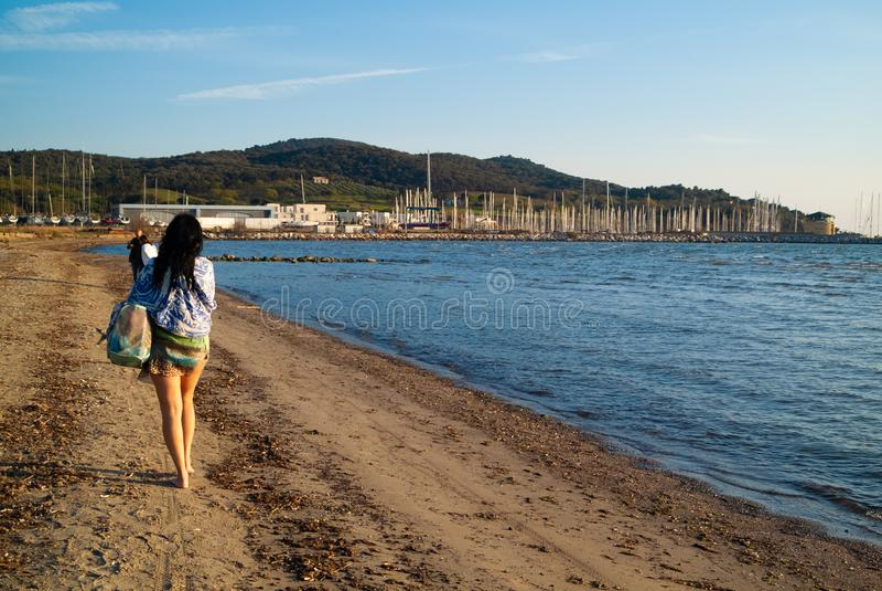 Puntone Scarlino, Maremma Τοσκάνη, Ιταλία Ώριμη γυναίκα που περπατά στην παραλία στοκ εικόνα