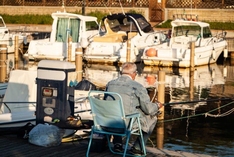 Puntone Scarlino, Maremma Тоскана, Италия Старший человек удя на заходе солнца на зоне маленькой лодки стоковое изображение
