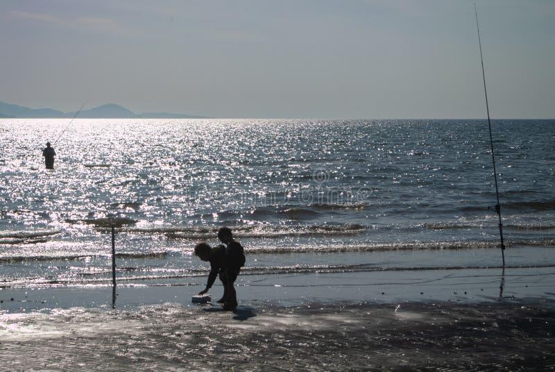 Puntone Scarlino, Maremma Toskana, Italien, Fischer, der bei Sonnenuntergang während Kinder spielen um den Strand fischt stockbild