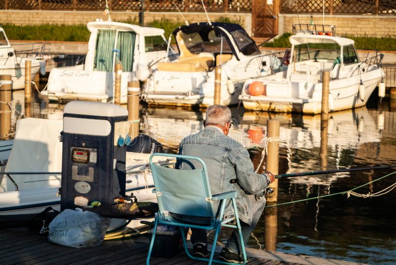 Puntone Scarlino, Maremma Tuscany, Italy. Senior man fishing at sunset on the small boat area. Puntone Scarlino, Maremma Tuscany, Italy - circa April 2019 stock image