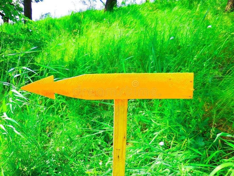 Puntos amarillos de madera de la flecha a la izquierda fotos de archivo