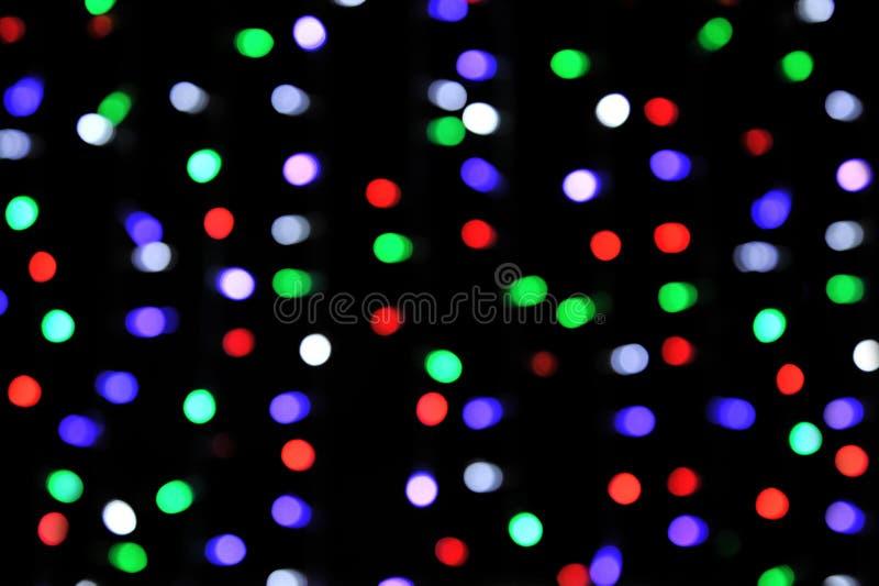 Puntos culminantes multicolores, guirnaldas de la Navidad sin foco foto de archivo libre de regalías