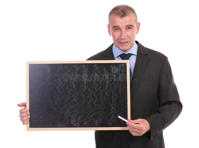 Puntos del hombre de negocios con tiza en la pizarra imagen de archivo
