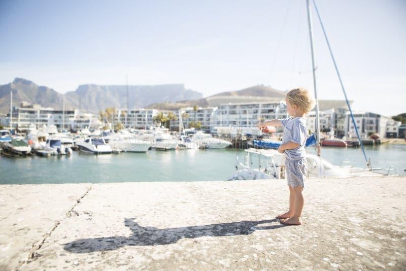 Puntos descalzos del niño al yate de lujo en puerto fotografía de archivo libre de regalías