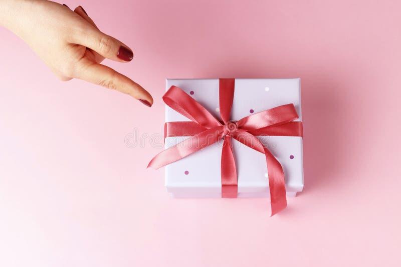 Puntos femeninos de la mano a la caja de regalo con la cinta en el fondo rosado, visión superior foto de archivo