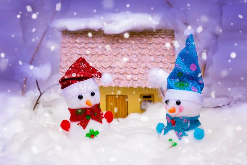 Pupazzi di neve del giocattolo sui precedenti della casa durante le precipitazioni nevose Natale Celebration_ immagine stock